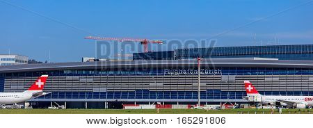 Kloten, Switzerland - 29 September, 2016: the main building of the Zurich Airport, Swiss International Air Lines jets standing at it. The Zurich Airport is the largest airport in Switzerland and the principal hub of Swiss International Air Lines.