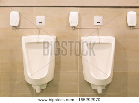 White automatic urinal for men on tile wall in toilet.