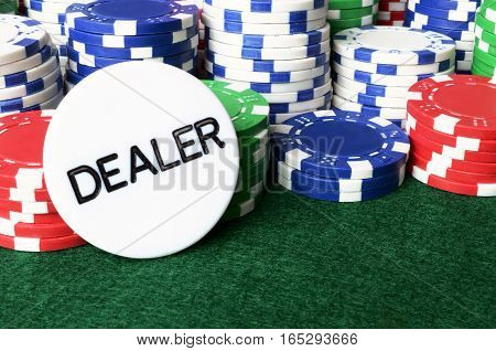 A close up image of stacked red,white,and blue poker chips with the white dealers chip.