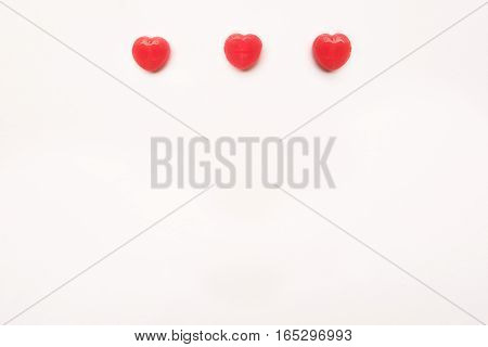 three Red Valentine's day heart shape candy line on white paper background. Love Concept. Minimalism style. Knolling top view.