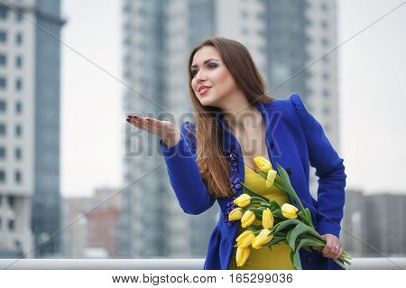 Young attractive girl in a blue coat and yellow dress holding a bouquet of yellow tulips. Spring is coming to town. She sends an air kiss