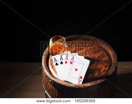 Playing Cards And Wine Glass Of Cognac On Barrel