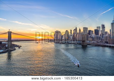 View of Brooklyn Bridge and Manhattan skyline at sunset