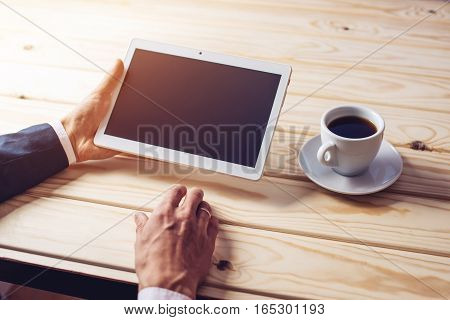 man businessman in suit using a digital tablet holding it in the office on the background of wooden table with Cup of coffee