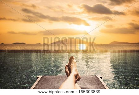 Relaxing in summer, a man laying on sunbathing bed on the island in sunset