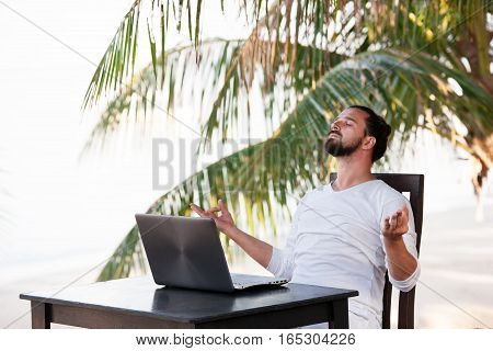 telecommuting, businessman relaxing on the beach and doing yoga with laptop and palm, freelancer workplace, dream job