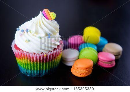 Colorful Rainbow valentine heart cupcake with macaron.