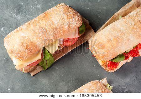 Ciabatta sandwich with salami on a light gray background