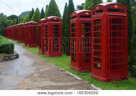 Numerous old and renovated red telephone boxes in Thailand Park