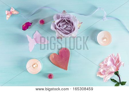 A Valentine day card with a rose flower, a paper butterfly, sweets, a candle, a little cutout heart, watercolour drawings and copyspace, slightly toned
