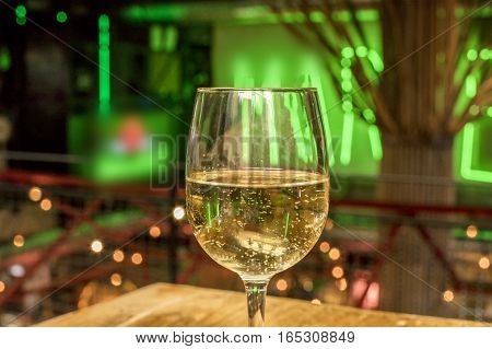 A glass of white wine on a blurred background of lights. Selective focus
