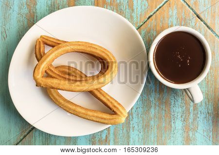 A plate of churros, traditional Spanish, especially Madrid, dessert, particularly for Sunday breakfast, with a cup of hot chocolate, shot from above on a teal table with a place for text