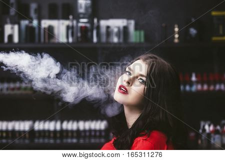 Young Beautiful Brunette Woman With Fashion Makeup At The Bar With A With Vapor