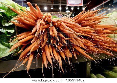 Organic carrots on market shelves. Granville Island Organic Market. Vancouver. British Columbia. Canada.