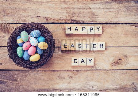 Colorful Easter Egg In The Nest And Wood Text For Happy Easter Day On Wood Background With Space