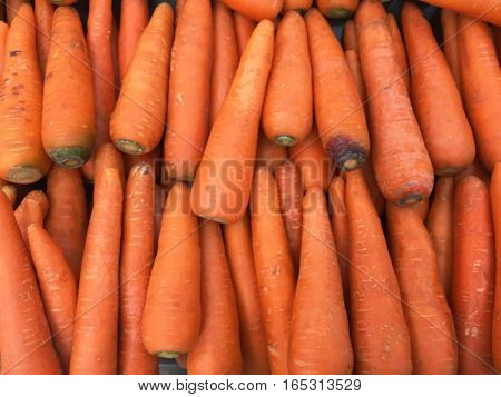 Carrots spread out on the counter for sale