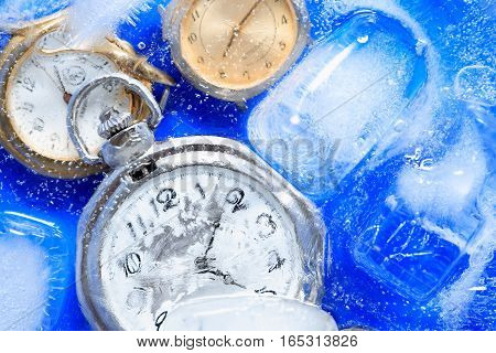 Few watches closeup under frozen water background with ice