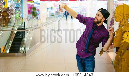 Young Man With A Beard In A Plaid Shirt And A Tie And Cap, Make Selfie With A Movie Hero In Mall