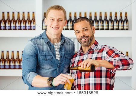 Two handsome and smiling men pouring glass with beer from bottle