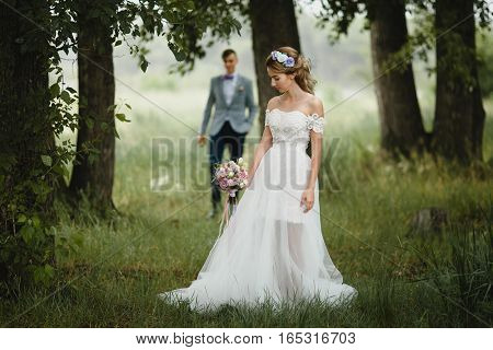 Beautiful bride with bouquet walking among the trees. In the background is approaching the groom