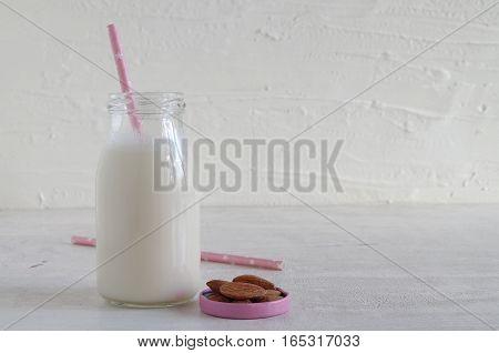 frische vegane Mandelmilch in einer Milchflasche mit Mandeln