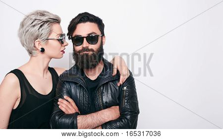 young modern stylish couple in urban black clothes over white background with copy space. Fashion bearded young man and blonde short hair woman couple embracing