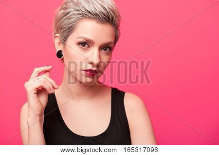 Close-up of Hipster girl with short blond hair, piercing and ear tunnels over pink color background. Fashion model