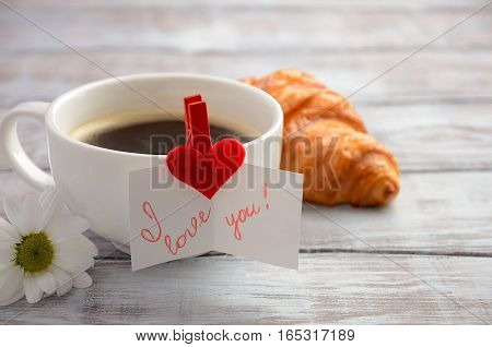 Cup of fresh morning coffee with croissant. Valentine's day concept. Horizontal, copy space.