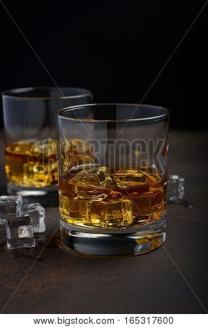 Glass of whiskey with ice on the old rusty background, selective focus, copy space