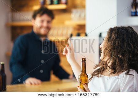 Curly-haired brunette with bottled beer talking and smiling at unfocused bartender