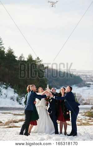 Best Man With Bridesmaids And Newlyweds Drinking Champagne On Frost Winter Wedding Day And Looking U