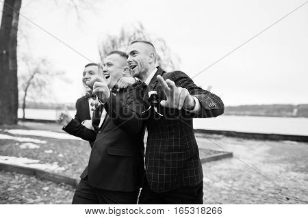 Groom With Best Mans At Cold Winter Wedding Day. Black And White Photo
