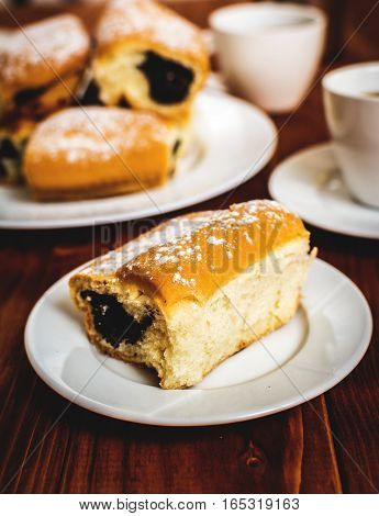 Baked sweet buns with poppy and coffee on wood table