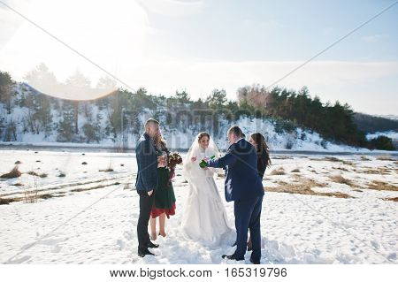 Best Man With Bridesmaids And Newlyweds Drinking Champagne On Frost Winter Wedding Day.