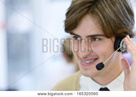 Smiling young call center executive at startup office.