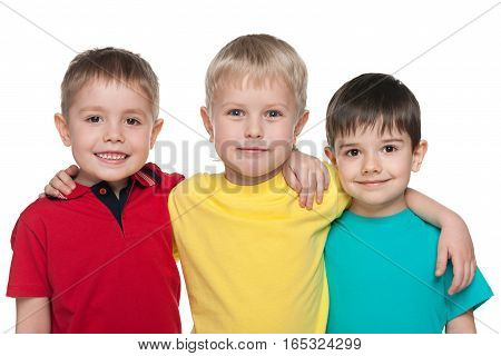 Three little boys are standing together on the white background