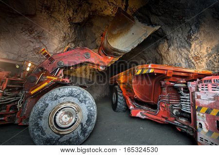 Gold mining underground. Loading truck with golden ore in the tunnel.