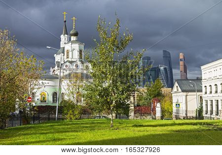 Moscow contrasts - old Orthodox Church and the modern business center against the gray autumn sky.