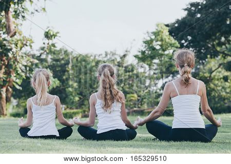 Mother and daughters doing yoga exercises on grass in the park at the day time. People having fun outdoors. Concept of friendly family and of summer vacation.