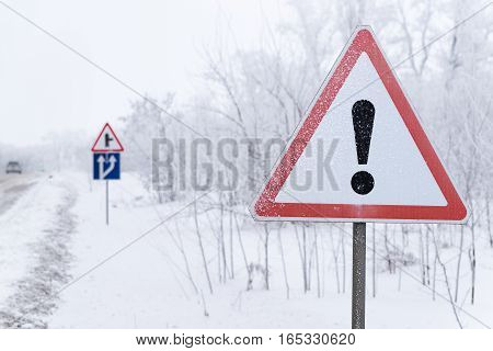 The road sign is on the snowy side