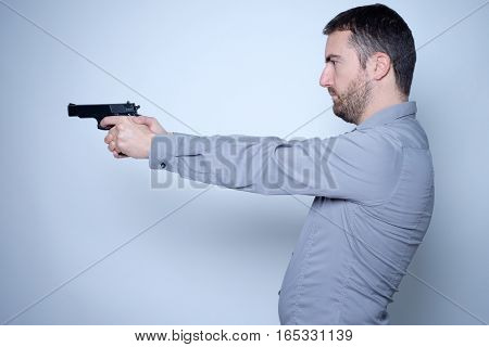 Man Holding A Gun In His Hands Ready To Shoot