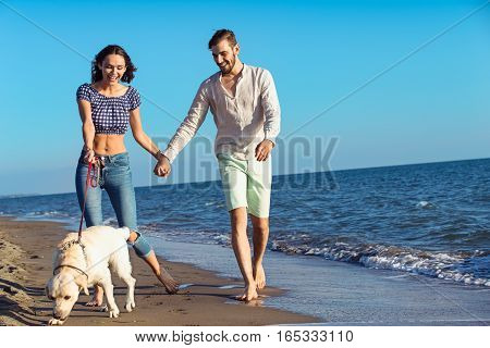 two young people running on the beach kissing and holding tight with dog.