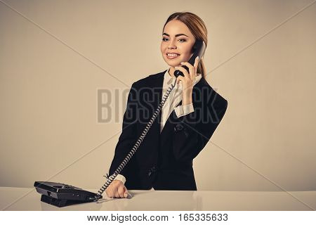 Portrait of young woman sitting at the table and working. Nice manager sitting at the table and making call.