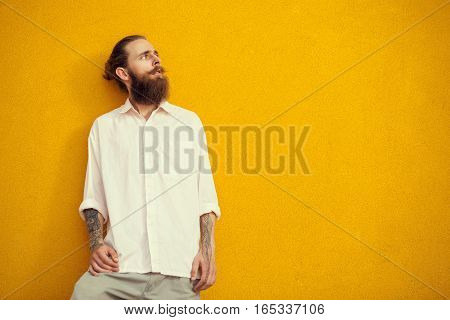 Bearded And Tattooed Man Posing On Yellow Wall