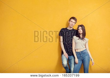 Couple Posing In Fashion Style On Yellow Wall