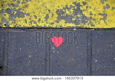 Red heart of foil on wet pavement with yellow paint. Background texture.