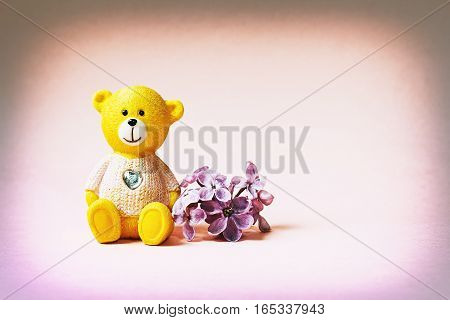 Teddy Bear and lilac flowers on a pink background. Cute background with space for text and greetings. Effect of the old film.