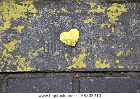 Yellow heart of foil on wet pavement. Background texture.