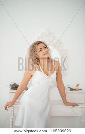 Curly Blonde Girl In A White Silk Gown Boudoir Robe Background Mirror.