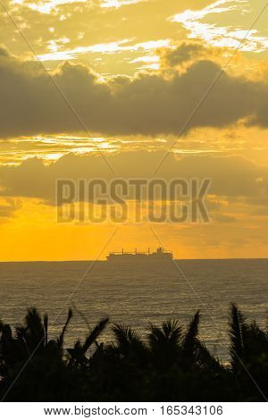 Ship silhouetted colors crossing on ocean seas dawn morning landscape